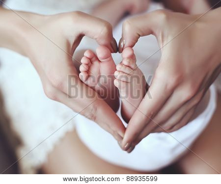Baby Feets In Mom Hands Holding Them In Heart Shape