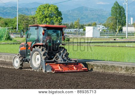Tractor Tilling A Rice Field
