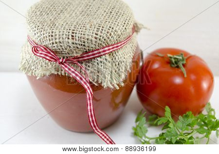 Glass Jar Of Homemade Ketchup And A Tomato
