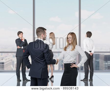 Happy Young Professionals Are Standing In A Contemporary Glass Office In New York. Handshake As A Co