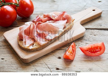 Hearty Bread With Ham  Bacon  On A Wooden Board