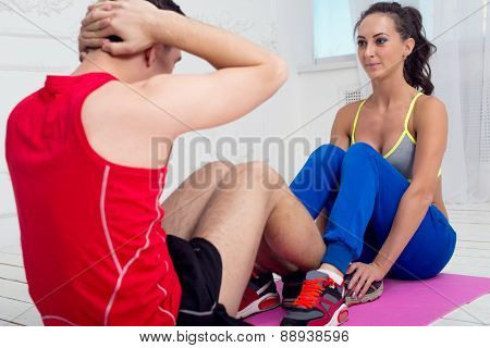 Active sportive man doing abdominal exercises crunches on floor in gym with the help of woman concep