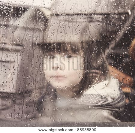 Child Looking Through The Car Window On A Rainy Day