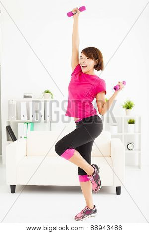 Young Woman Exercising With Dumbbells In Living Room