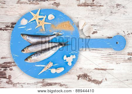 Fresh Anchovy Fish On White And Brown Wooden Kitchen Board.