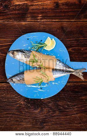 Fresh mackerel fish on wooden kitchen board.