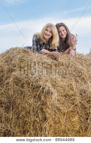 Portrait of student friends lying on big round straw bale