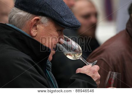 PRAGUE, CZECH REPUBLIC - NOVEMBER 11, 2012: Elderly man tastes young wine during the celebration of Saint Martin Day in Prague, Czech Republic.