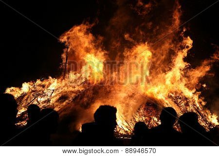 BURG, GERMANY - APRIL 23, 2011: People look at the traditional Easter bonfire in the Lusatian village of Burg in Spreewald Region, Lower Lusatia, Brandenburg, Germany.