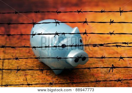 Piggy Bank On Grunge Background Against Barbwire