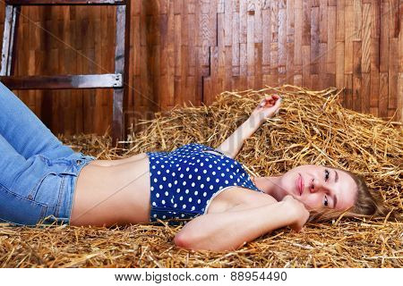 Beautiful Young Smiling Girl With Long Blond Hair In Jeans Lying On Hay