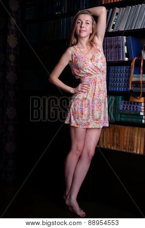 Beautiful Girl With Blond Hair In Short Dress Standing Next To Shelves Of Books