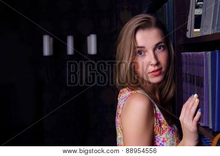 Closeup Of Beautiful Girl With Long Blond Hair Near Shelf Of Books Looking At Camera