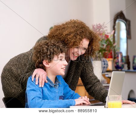 Happy Mother And Son Using Laptop At Home