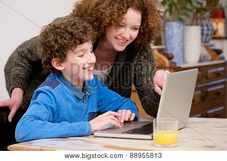 Smiling Mother And Child Using Laptop At Home