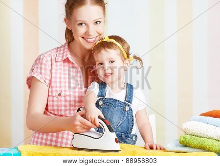 Family Mother And Baby Daughter Together Engaged In Housework Iron Clothes