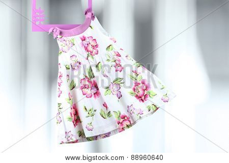 Fashion Baby Dress Hanging On A Hanger On A Gray  Background
