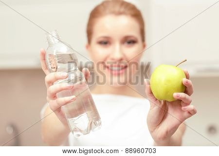 Lady holds bottle of water and apple