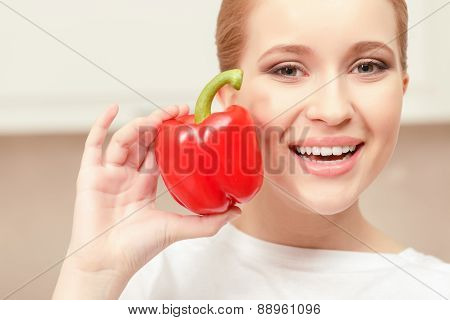Young woman smiling and holding red pepper