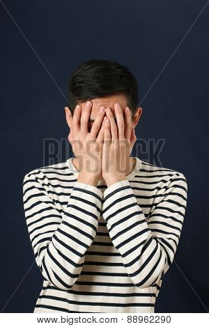 Disappointed young Asian man covering his face by palms