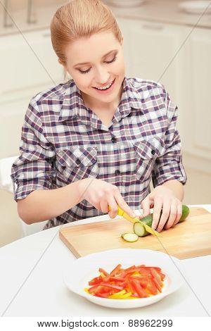 Woman cuts cucumber and pepper