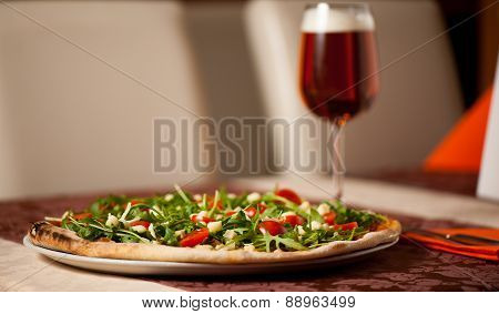 Pizza With Rucola, Cherry Tomatoes And A Glass Of Beer On A Teble Of Italian Restaurant