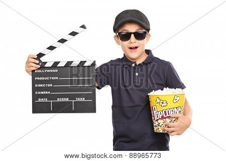 Little kid with a beret and sunglasses holding a box of popcorn and a movie clapperboard isolated on white background