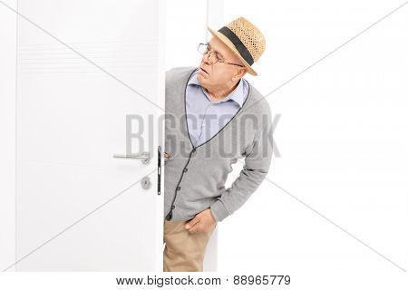 Curious senior gentleman looking at something behind a white door isolated on white background
