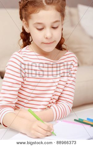Little girl sitting and drawing