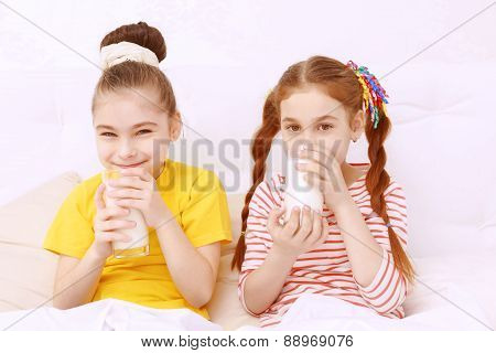 Bright dressed children drinking milk
