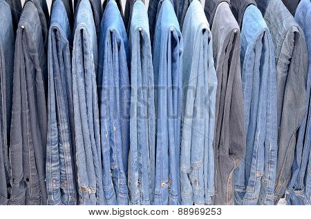 Many Colored Jeans Hanging On Hangers
