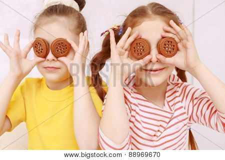 Two funny girls posing with cookies