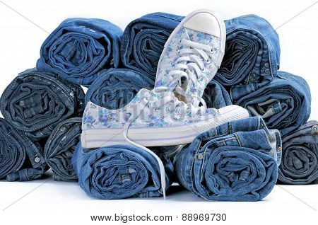Pair Of Sneakers And Stack Of Rolled Colored Jeans