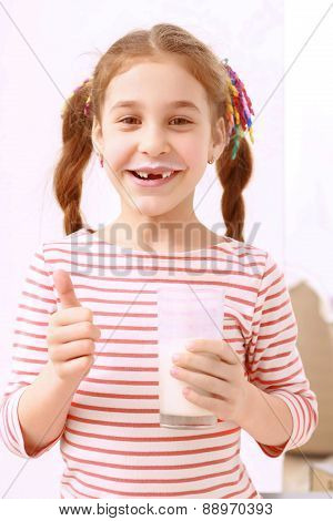 Little girl posing with glass of milk