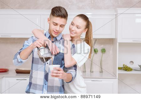 Handsome guy pouring out coffee for girl