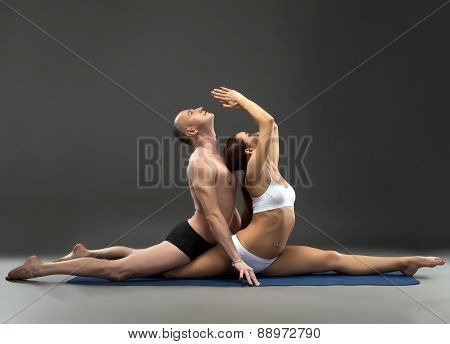 Sensual composition of yogis, on gray background