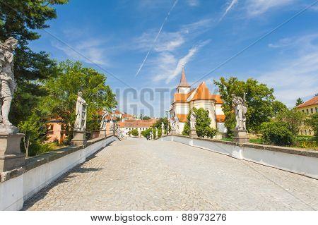 Baroque bridge with statue and a church in Namest nad Oslavou, Czech Republic