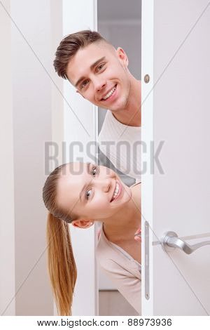 Two nice persons emerge from behind door