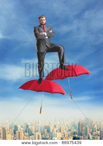 Businessman on umbrellas in the air