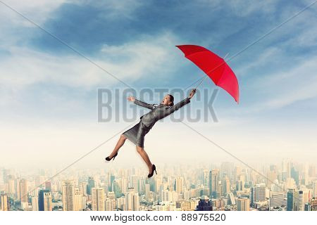 Scared woman flying in the sky with umbrella
