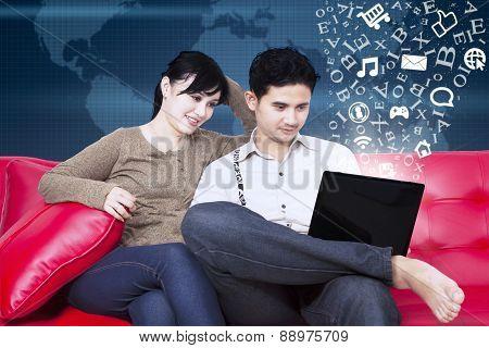 Happy Couple Sitting On Sofa With Flying Alphabet