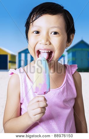 Happy Little Girl Eating Ice Cream At Coast