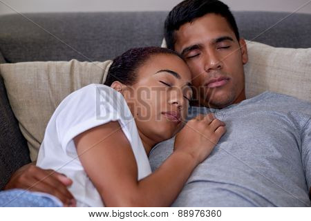 portrait of romantic married couple sleeping on sofa couch in home living room