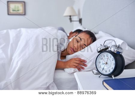 alarm clock young couple sleeping comfortably in bed at home