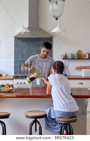 husband is pouring coffee for his wife in kitchen early morning breakfast routine