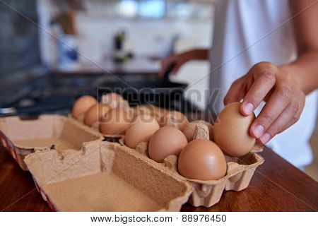 woman preparing early morning eggs breakfast on stove in home kitchen