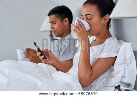 young couple with mobile phone sending emails working from bed