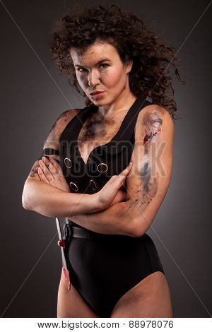 Beautiful young athlete woman with military style clothing and dirty face, wound and blood.