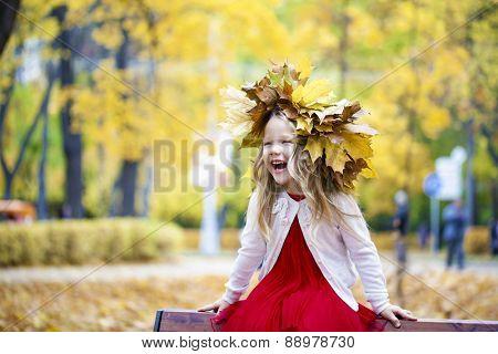 Portrait of beautiful little girl, against background of autumn park