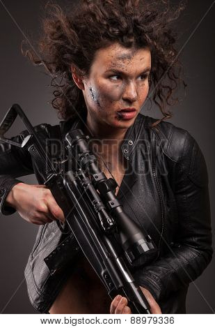 Sexy military woman posing with sniper gun. With blood, dirty face and wound.